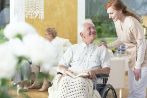 A man in his old age ia a wheelchair talking to a personal assis