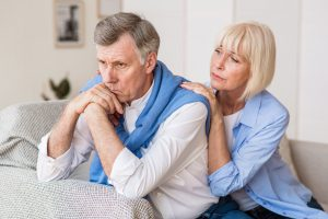 Senior woman consoling husband after arguing at home