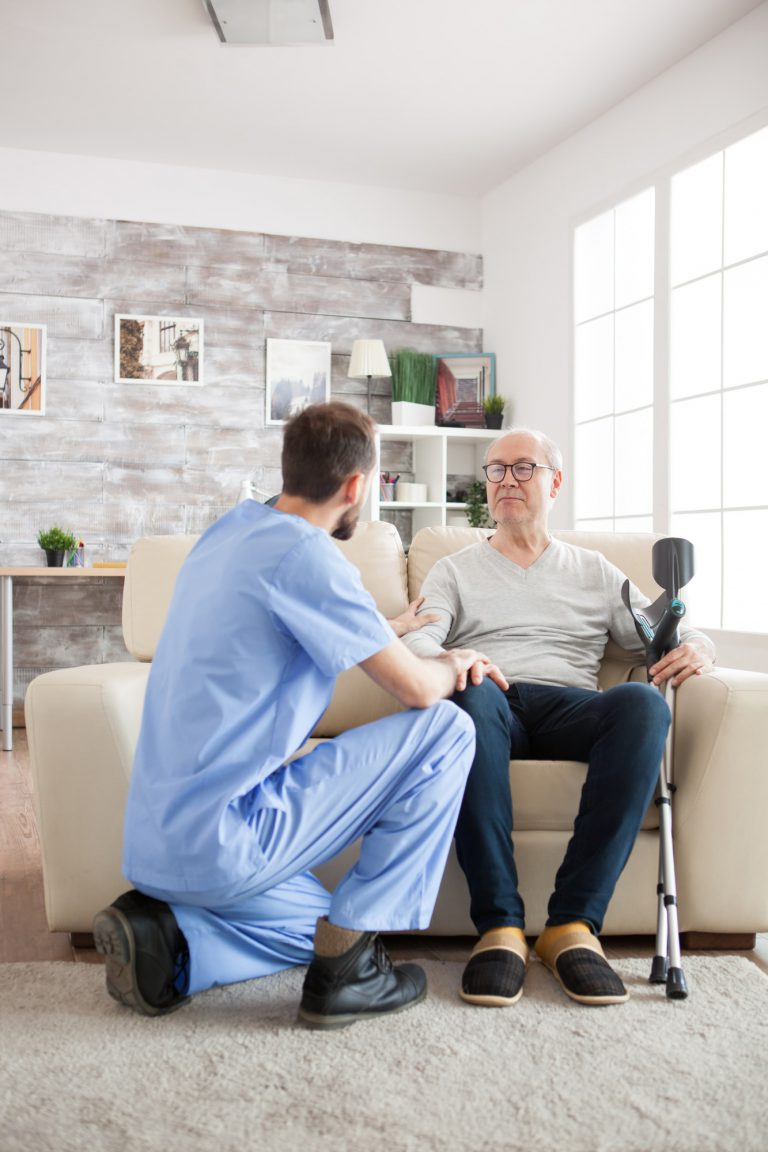 Young doctor holding old man arm in nursing home
