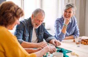 Group of senior people playing board games in community center club