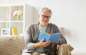senior man on sofa reading book at home